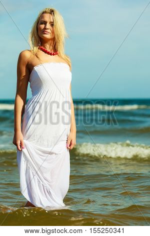 Leisure spare time activities. Young woman chilling out on the beach. Lady spending free moments outside. Attractive girl has white dress.
