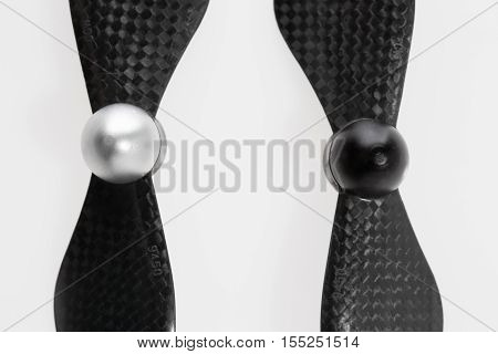 Close up of set of two carbon fiber self-tightening propellers for a quadcopter drone on white background. Size is 9450. One is clockwise and another one is counterclockwise rotation direction. High angle view.