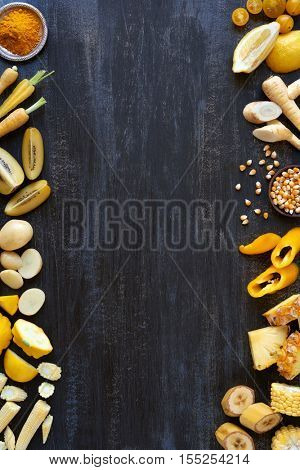 Food background design with yellow hued fresh fruit and vegetables border frame shot overhead