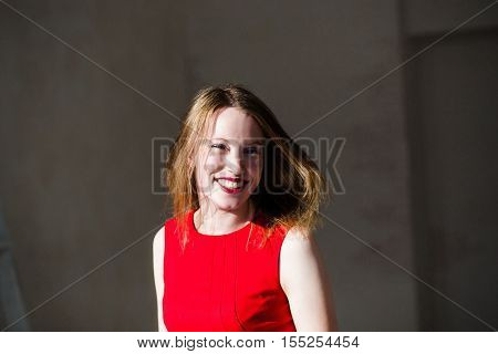 Bright image of Smiling blonde in red dress with fluttering hair have fun at light room in sunny rays.