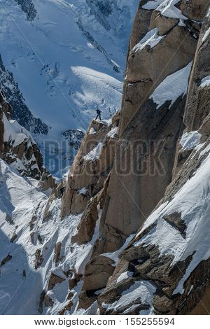 Two rock climbers working together to scale a rockface in the Alps in winter.