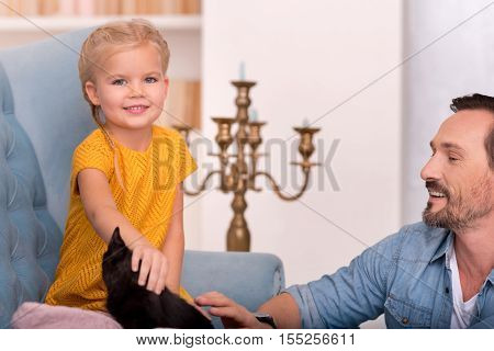 Good mood. Pretty nice cute girl sitting near her father and looking at you while stroking a black kitten