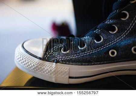 Sport fashion. Closeup navy blue fashionable sneakers on shop shelf