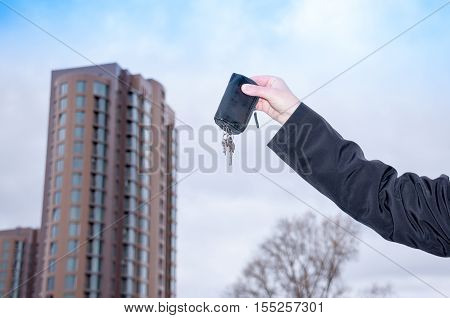 Man's hand holding the keys to a new apartment