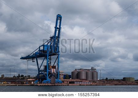 A crane and silos in an industrial harbour by the sea standing idle.