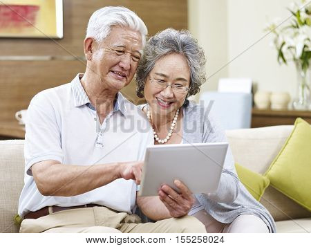 senior asian couple sharing a tablet computer at home