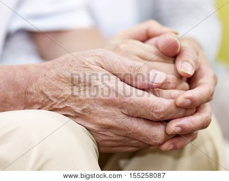 close-up of wrinkled hands of a loving senior couple held together