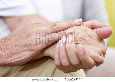 close-up of a senior male's hands touching caressing a senior female's hand