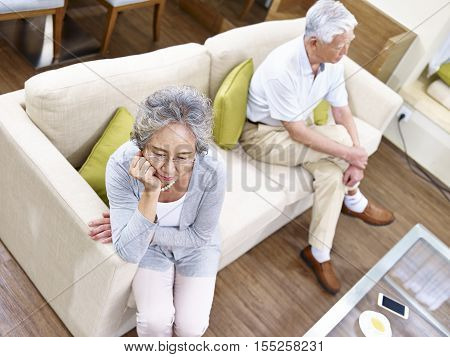 senior asian couple sitting on couch at home angry at each other high angle view