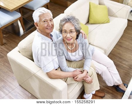 loving senior asian couple sitting on couch at home high angle view