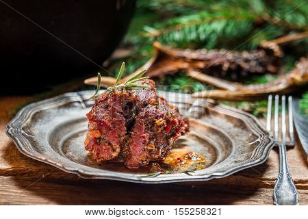 Metal plate with baked venison on old wooden table