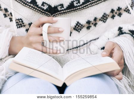 Close up of woman hands holding a book and a cup of coffee. Student winter home education concept.