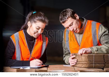 Workers with cardbord boxes checking its quality at the factory
