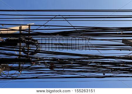 Messy cables attached to electrics pole Including electrics phone and others communication cables Bangkok Thailand.