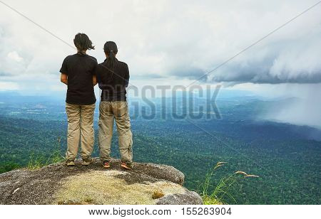 Two friends stand together at the cliff and see rain which is coming over tropical rain-forest.