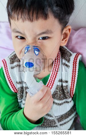 Closeup Of Angry Asian Child Holds A Mask Vapor Inhaler For Treatment Of Asthma. Breathing Through A