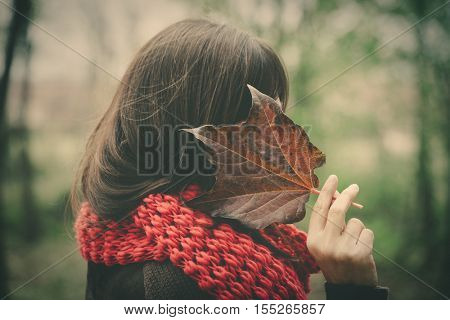 woman in autumn park hide face with leaf retro colors closeup side view