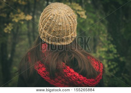 back view of woman with wool cap and scarf outdoor autumn winter day in wood closeup