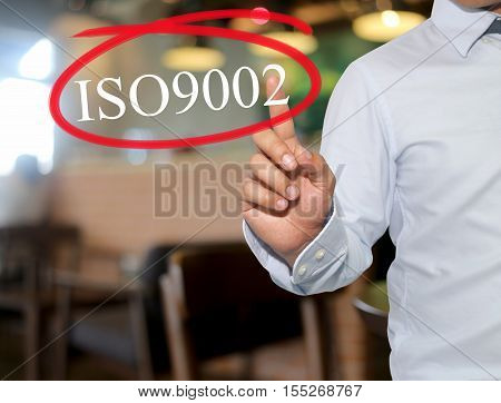 Hand of man touching text ISO9002 with white color on blur interior backgroundconcept of adoption to promote your business for organization.