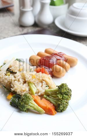 Fried rice and sausage on white dish in a restaurant.