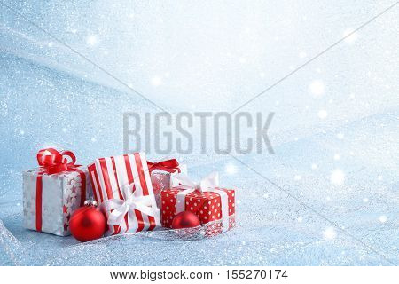 Christmas gift boxes and balls on abstract background