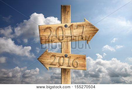 Wood sign of 2016 in left and 2017 in right on blue sky backgroundconcept of a start to new year.