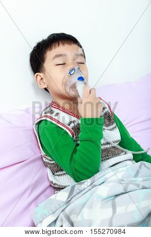 Asian Child Closing Eyes And Holds A Mask Vapor Inhaler For Treatment Of Asthma.