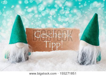 German Text Geschenk Tipp Means Gift Tip. Christmas Greeting Card With Two Turqoise Gnomes. Sparkling Bokeh Background With Snow. German Text Frohes Fest Means Merry Christmas