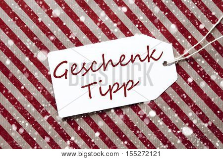 German Text Geschenk Tipp Means Gift Tip. One Label On A Red And Brown Striped Wrapping Paper. Textured Background With Snowflakes. Tag With Ribbon.