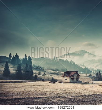 Beautiful landscape in the mountain village. Foggy morning with dramatic blue sky. Vintage toning effect. Carpathians, Ukraine, Europe. Exploring beauty world
