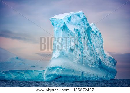 Antarctic iceberg of unusual form in the snow floating in open ocean. Pastel sunset sky in the background. Beauty world.