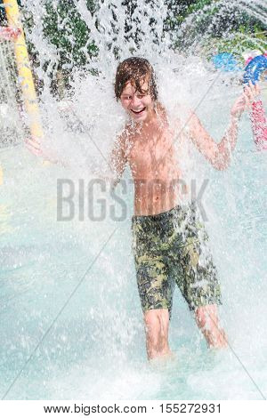 Smiling boy getting splashed with water at a waterpark
