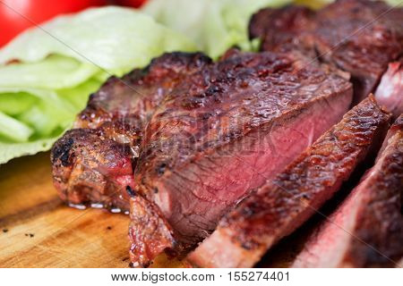 medium-rear grilled rib-eye steak with vegetables on wooden background