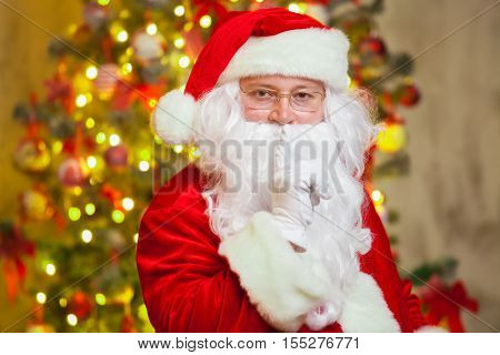Portrait of Santa Claus forefinger by his mouth on background of sparkling firtree