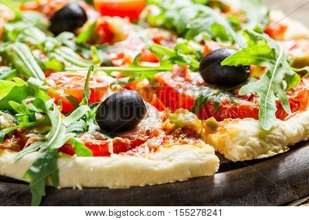 Closeup of fresh pizza with vegetables on old wooden table