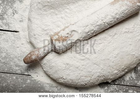 Rolling pin with flour close up on wooden table in bakery top view. Bakery background