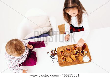 Kids cooking pastry, free space. Top view on sister preparing berry cakes and her brother sitting on kitchen table. Homemade bakery, children culinary, pastry making concept