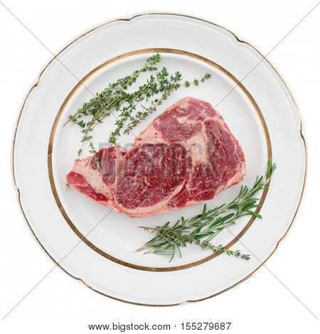 Raw rib-eye steak with aromatic herbs on plate, isolated on white