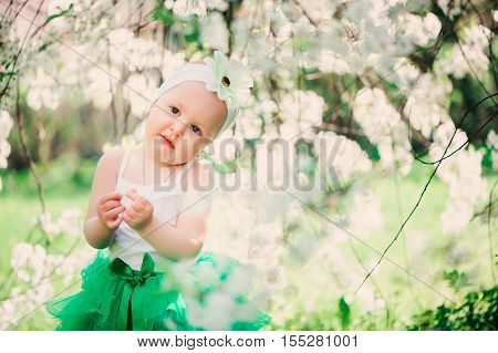 spring portrait of cute baby girl in green skirt enjoying outdoor walk in blooming garden