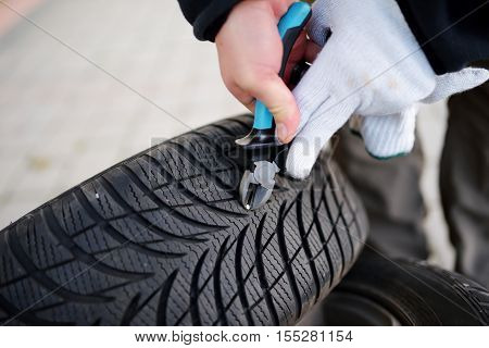 Pulling a nail out of tire with a tool