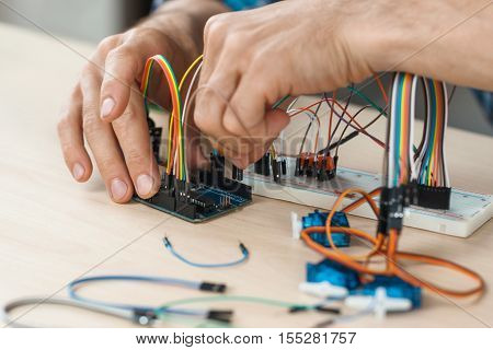 Electronic component connected with breadboard in laboratory. electrical engineering with cables and controller. Modern technologies, electronics, diy product engineering