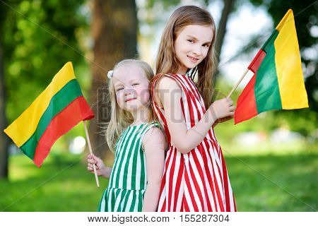 Two Pretty Little Sisters Holding Tricolor Lithuanian Flags