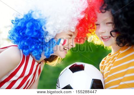 Two Funny Little Sisters Supporting And Cheering Their National Football Teams