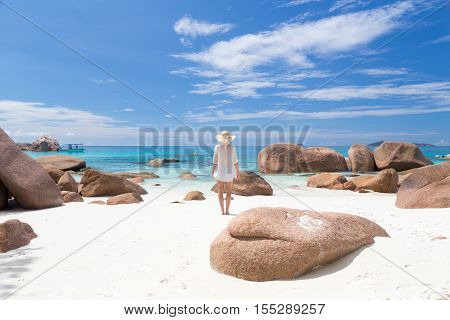 Woman wearing white loose tunic over bikini and beach hat on Anse Lazio beach on Praslin Island Seychelles. Summer vacations on picture perfect tropical beach concept.