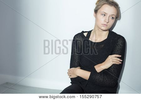 Sad Woman Sitting Beside White Wall