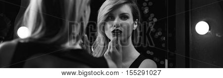 Black and white photograph of women applying lipstick