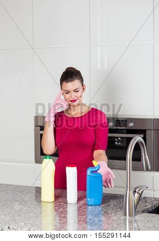 Woman Wearing Cleaning Gloves Standing In A Kitchen