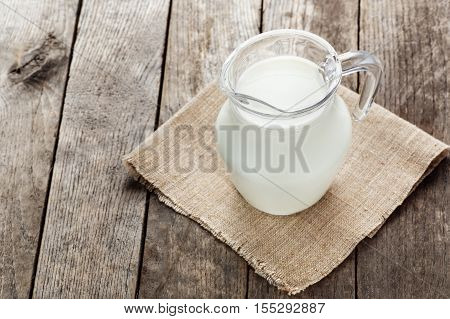 glass jug with milk on wooden background. Jug of milk on wooden table. Milk jug with napkin on old wooden table copy space
