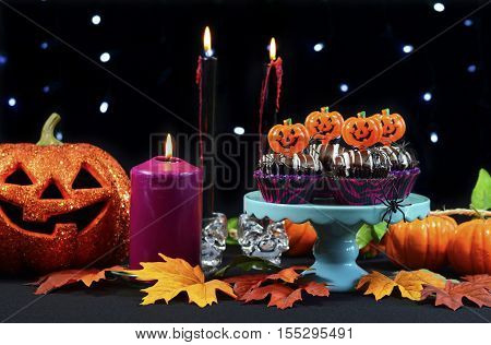 Halloween Party Table With Chocolate Cupcakes, Spiders, Pumpkins