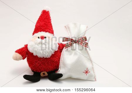 Cute stuffed toy Santa Claus and present on white background. Santa Claus doll and white bag.